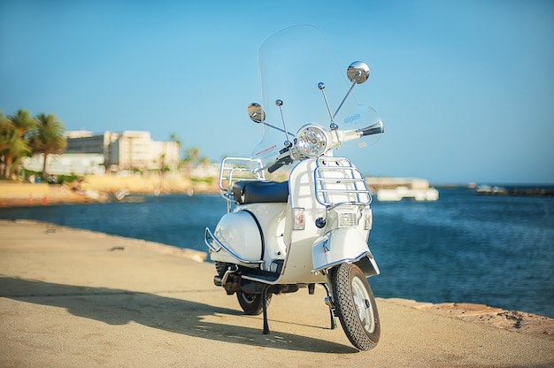 White retro scooter on the beach. touristic embankment Premium Photo