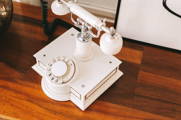 White retro telephone on a wooden table. close-up. Premium Photo