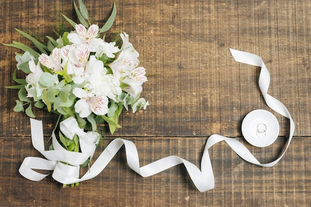 White ribbon and flower bouquet with wedding rings on plate over wooden desk Free Photo