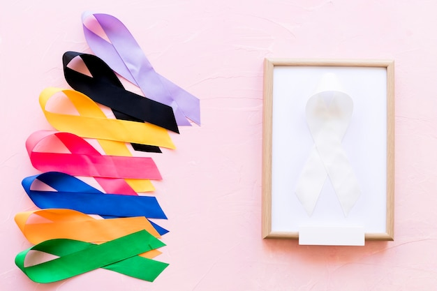 White ribbon on white wooden frame near the row of colorful awareness ribbon Free Photo