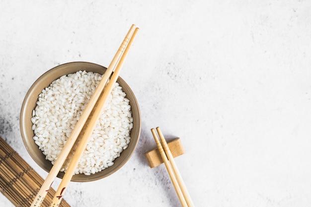 White rice in bowl near bamboo mat Free Photo