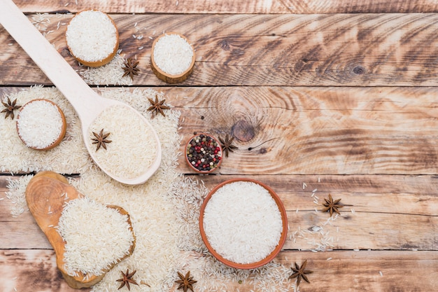 White rice in bowl; spoon and on tree stump with dry spices over textured wooden surface Free Photo