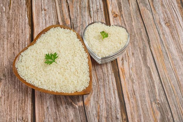 Il riso bianco viene posto in una tazza sul pavimento di legno. Foto Gratuite