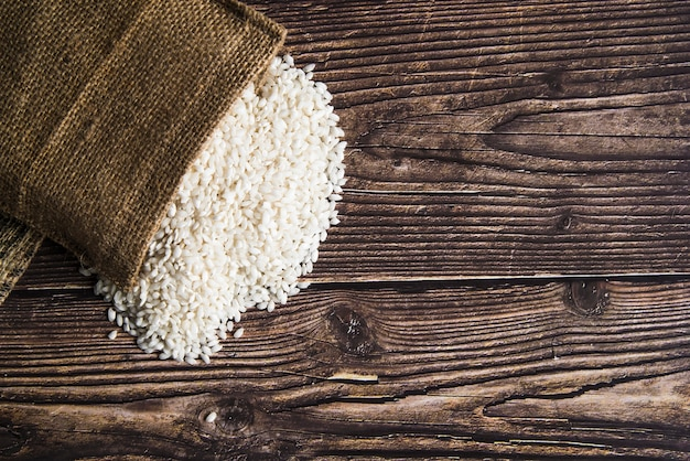 White rice scattered from sack on table Free Photo