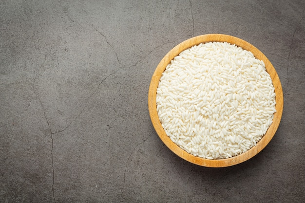 White rice on small wooden plate place on dark floor Free Photo