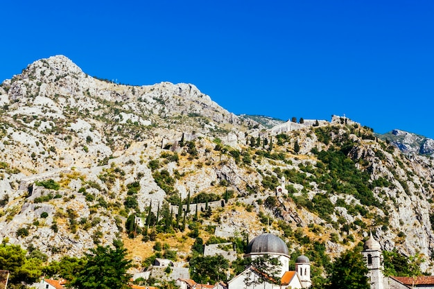 White rocky mountainside with green trees against a blue sky Free Photo