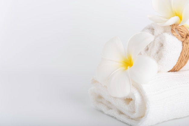 White rolled towels decorate with frangipani flowers spa object on white Premium Photo