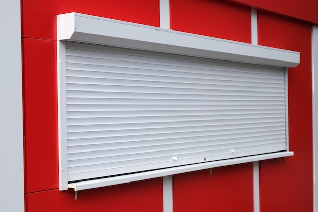 White roller shutters at a red kiosk. Premium Photo