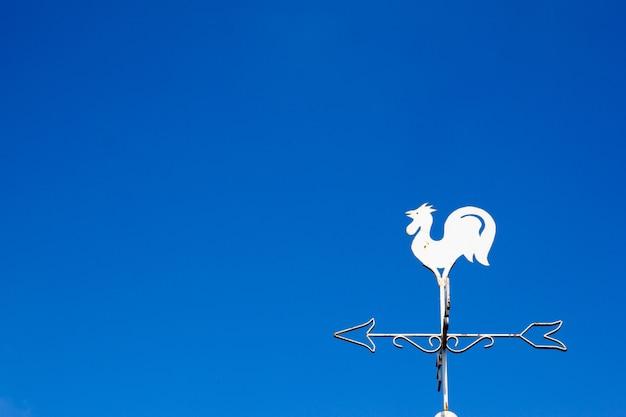 White rooster weather vane show the wind direction on blue sky background Premium Photo