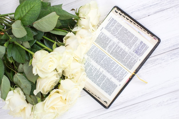 White roses and the bible. white roses and the bible on a white wooden background Premium Photo