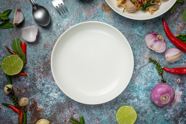 A white round empty  plate among of spices ingredients Free Photo