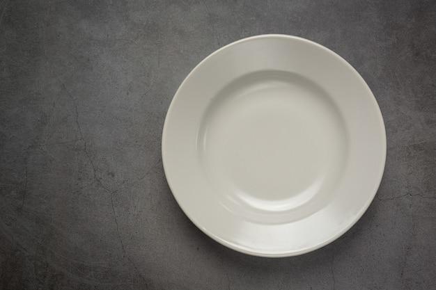 A white round empty  plate on dark surface Free Photo