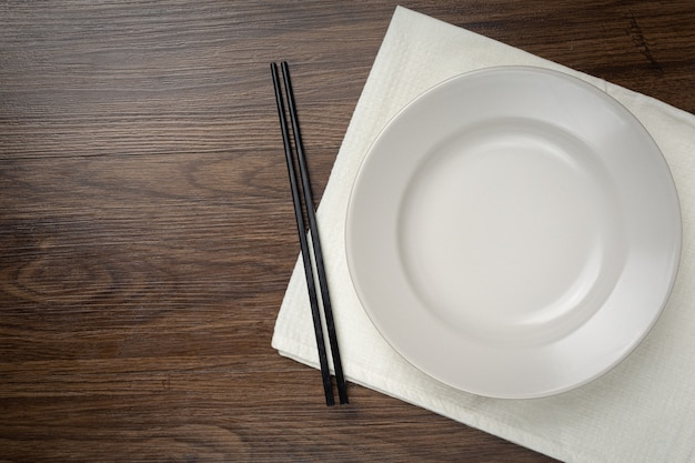 A white round empty plates and chopstick on wooden table Free Photo