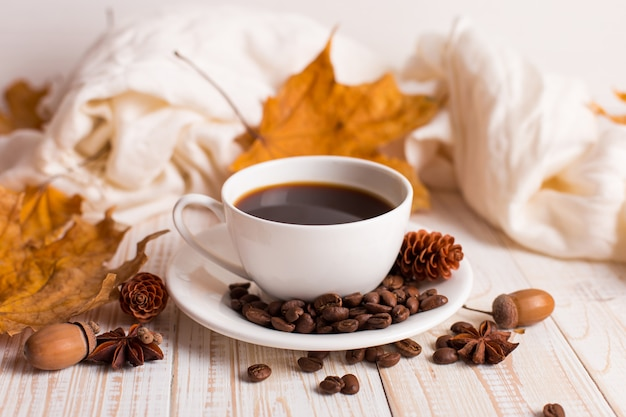 White scarf, a cup of coffee with scattered coffee beans, dry yellow leaves on a wooden table. autumn mood, copyspace. Premium Photo