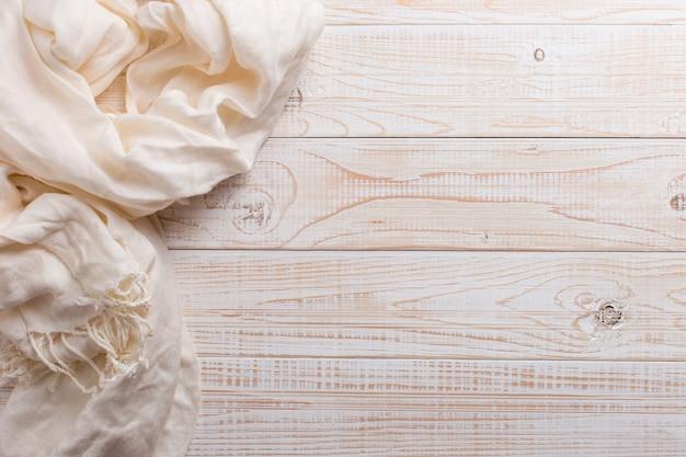 White scarf on a wooden table. autumn background, copyspace. Premium Photo