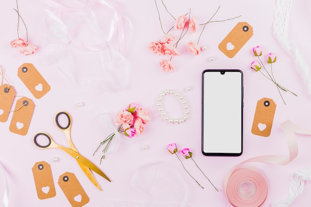 White screen display mobile phone with ribbons; roses; tags and pearl on pink backdrop Free Photo