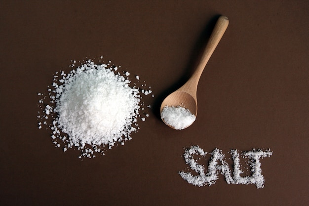 White sea salt with wooden spoon on brown Premium Photo