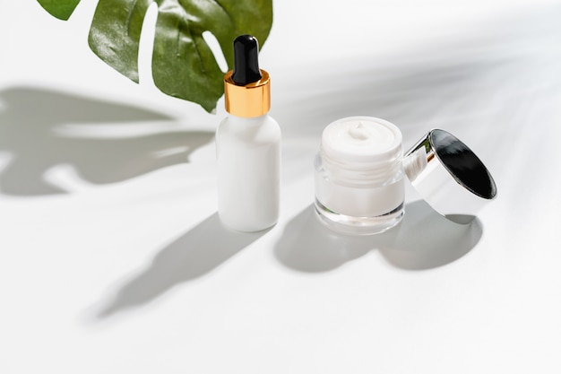 White serum bottle and cream jar, mockup of beauty product brand. top view on the white background. Premium Photo