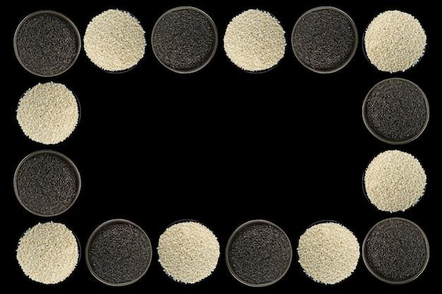 White sesame, black sesame seeds in a black bowlon black background Premium Photo