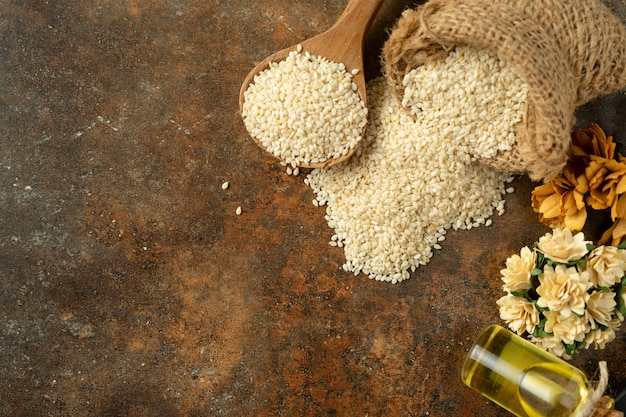 White sesame and sesame oil on wooden spoon. on rustic background top view Premium Photo