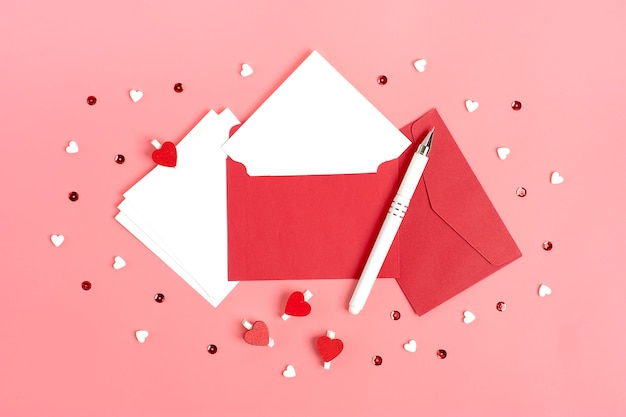 White sheet of paper, red envelope, gift box, tittle sparkles, pen on pink background Premium Photo
