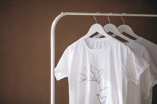 White shirts hanging in room Free Photo