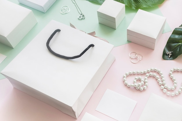 White shopping bag and gift boxes with jewelry on colored background Free Photo