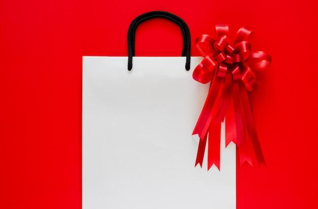 Белая хозяйственная сумка с красным бантом и лентой на красном. Premium Фотографии