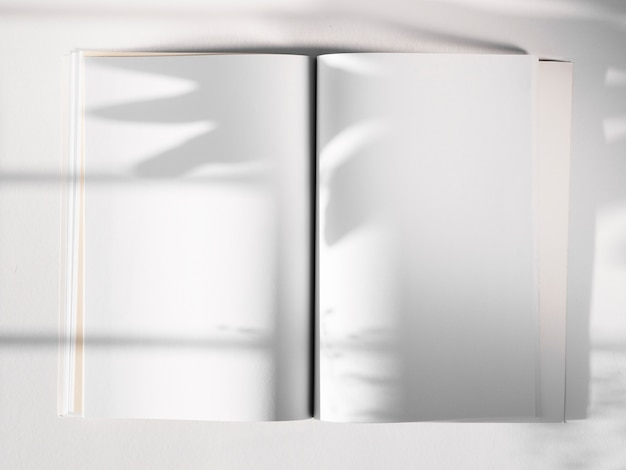 White sketch book on a white background with a leaf shadow Free Photo