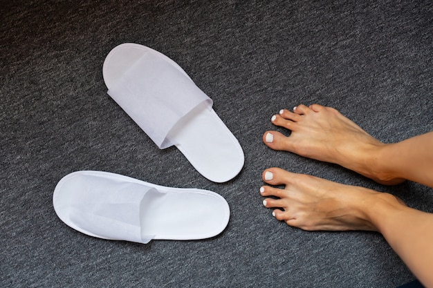 White slippers on rug and woman foots Premium Photo