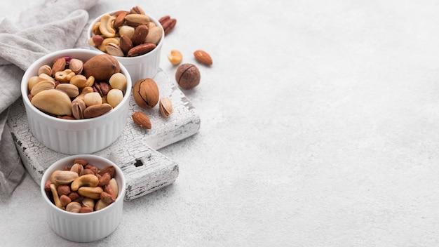 Белые миски, наполненные ассортиментом орехов, копировать пространство Premium Фотографии