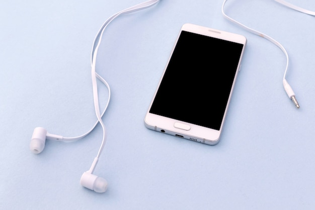 White smartphone and white headphones on blue background. Premium Photo