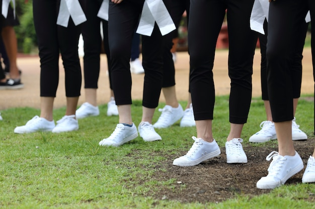White sneaker shoes of many women on grass ground Premium Photo