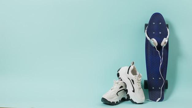 Белые кроссовки, синий скейтборд и белые наушники на синей поверхности Premium Фотографии