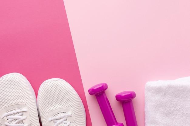 Sneakers bianche e pesi asciugamano rosa con spazio di copia Foto Gratuite