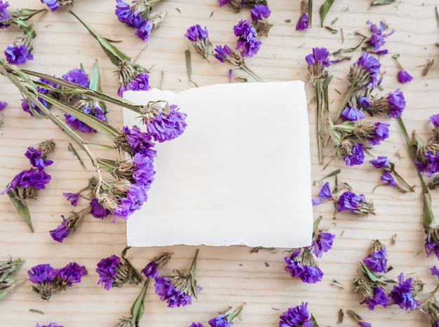 White soap bar on a wooden background with violet followers top view Premium Photo