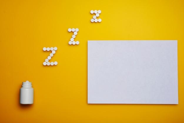 Белые somnifacient таблетки для z письмо и чистый лист бумаги на желтом фоне. копировать пространство Premium Фотографии