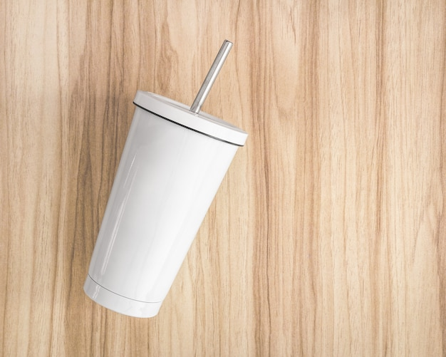 White steel mug with tube on wood background. insulated container for keep your drink. Premium Photo
