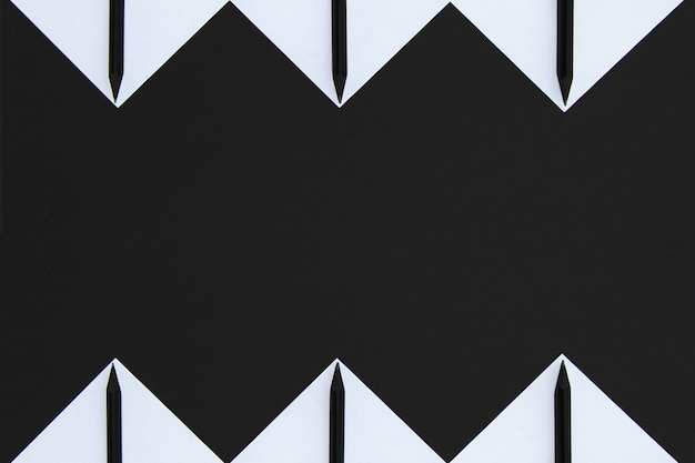 White stickers with black pencils lined with a geometric pattern on black Premium Photo