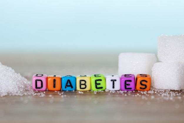 White sugar cube and colorful alphabet block of diabetes word on wooden table with light blue background , unhealthy a sweet food concept for 14th november campaign of world diabetes day Premium Photo