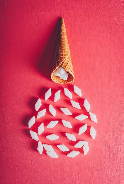 Zucchero bianco nella cialda del gelato su una tavola rosa-rosso. vista dall'alto. Foto Gratuite