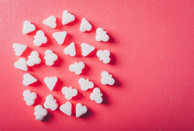 Vista superiore dello zucchero bianco su una tavola di rosa rosso Foto Gratuite