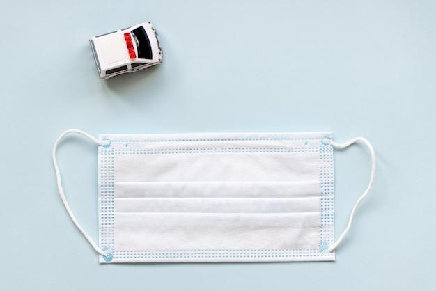 Белая хирургическая маска для рта и машина скорой помощи игрушки на синем фоне. во время концепции коронавируса covid-19. плоская планировка Premium Фотографии