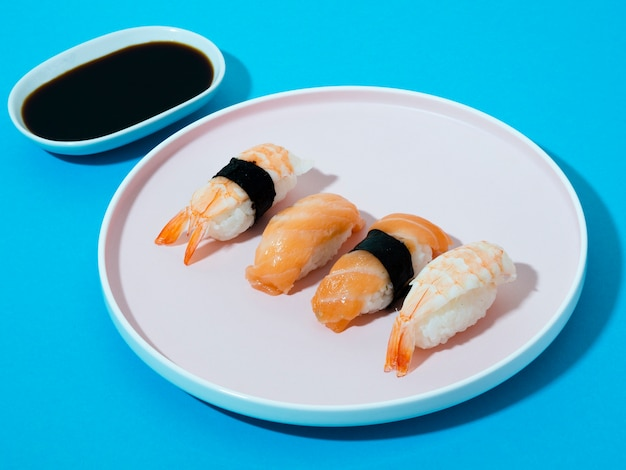 White sushi plate and soy sauce bowl on a blue background Free Photo