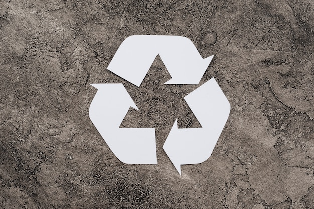 White symbol of recycling on dirty background Free Photo