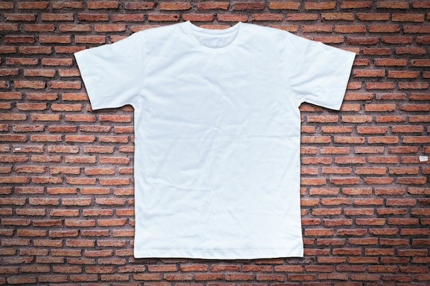 White t-shirt on brick wall background. Premium Photo