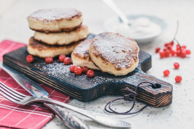 On a white table made of artificial stone is a wooden cutting board with five cottage cheese pancakes and red berries. on the table a red checkered napkin, sour cream, fork and knife. Premium Photo