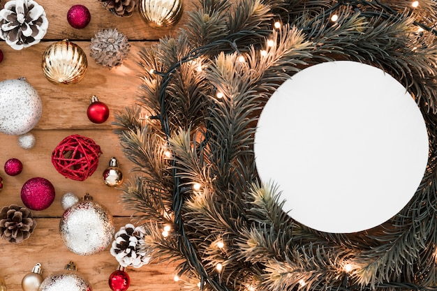White tablet between fir twigs and Christmas decorations Free Photo