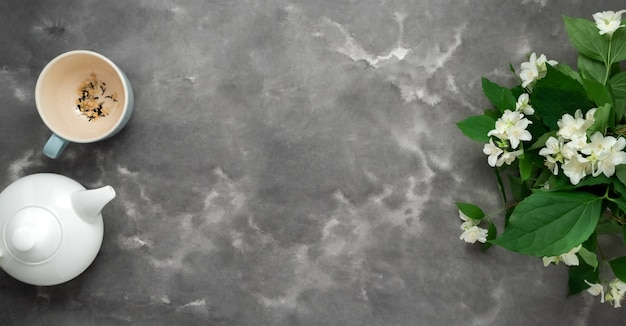 Белый чайник, травяной сухой чай, цветок жасмина, чашка, черный белый мрамор фон плоской планировки. время чая долго веб-баннер Premium Фотографии