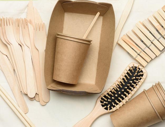 Белый текстильный мешок и одноразовая посуда из коричневой крафт-бумаги на зеленом фоне. вид сверху, концепция отказа от пластика, нулевые отходы Premium Фотографии